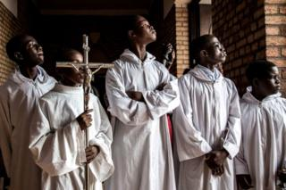 Altar boys try to get a glimpse at the current President of the Democratic Republic of the Congo, Felix Tshisekedi, ahead of a mass at the Notre dame de Kinshasa to commemorate the death of his father, Etienne Tshisekedi on February 1, 2019 in Kinshasa.