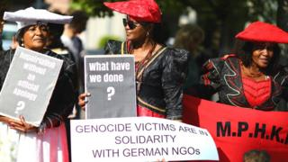 Namibians protest outside a ceremony in Berlin, Germany to hand back human remains from Germany to Namibia following the 1904-1908 genocide against the Herero and Nama - Wednesday 29 August 2018
