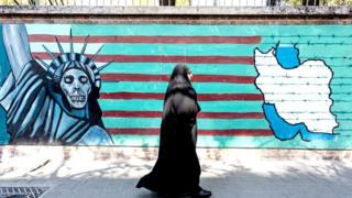 Mujer pasando por mural antiamericano en Teherán