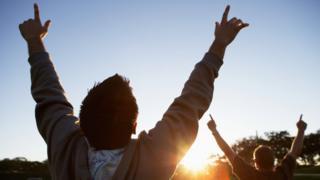 شاب يرفع يديه في إشارة إلى النصر أو الفوز
