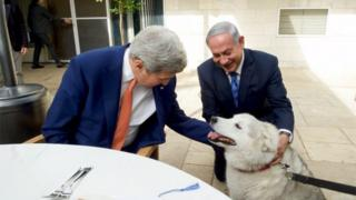 Israeli Prime Minister Benjamin Netanyahu (R) shows U.S. Secretary of State John Kerry his recently adopted dog Kaiya, during their meeting in Jerusalem November 24, 2015