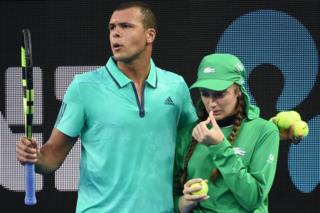 Jo-Wilfried Tsonga escorts ball girl Giuliana off court at last year's Australian Open