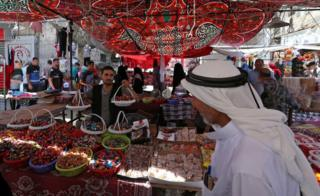 A vendor sells sweets as Palestinians shop in a market ahead of the upcoming Eid al-Fitr holiday marking the end of the Muslim holy month of Ramadan, in Rafah in the southern Gaza Strip June 14, 2018