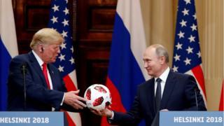 El presidente de Rusia, Vladimir Putin (der.), le entrega un balón de fútbol del Mundial al presidente de EE.UU., Donald Trump durante la cumbre en Helsinki.