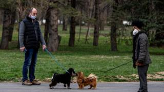 People walk their dogs in an empty park in Sofia, Bulgaria on 22 March 2020