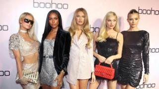 Celebrities posing in front of a Boohoo sign