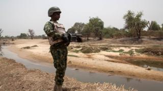 Soldier dey stand guard near di Yobe river wey separate Nigeria from Niger, for Damasak town for North East Nigeria on April, 25 2017