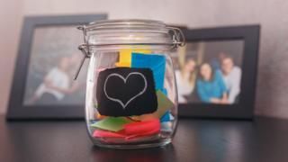 Memory jar in front of photo frames