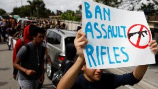 "A young protester carries a sign reading ""ban assault rifles"""