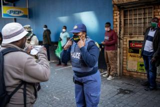 in_pictures A policewoman shows someone how to put their mask on
