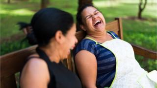 mulheres riem em um banco de parque