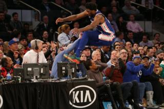 Philadelphia 76ers center Joel Embiid saves a ball from going out of bounds by jumping into the stands over actress Regina King (brown sweater) during the third quarter against the New York Knicks at Madison Square Garden.