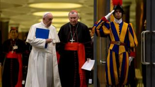 Pope Francis and Cardinal Pietro Parolin are saluted by a Swiss guard as they leave at the end of the afternoon session of the Synod of bishops, at the Vatican (Oct. 5, 2015)