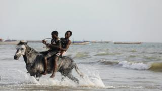 in_pictures Men ride a horse in the sea in Senegal