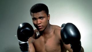 Muhammad Ali poses with gloves (undated photo)