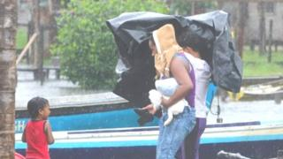 People carrying belongings and a pet leave their house as Hurricane Otto strikes in Bluefields, Nicaragua (24 November 2016)