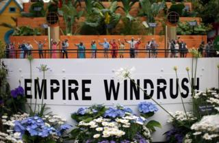 Small figurines adorn a replica of the deck of the Empire Windrush, part of the Windrush Garden on display in the Great Pavillion