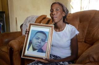 Betty Melamu holds up a picture of her daughter