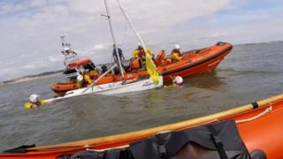 Lifeboat crews rescuing capsized dinghy off Newton Point at Porthcawl