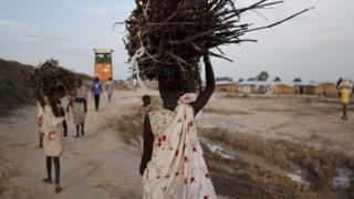 A young woman carries firewood after returning to the United Nations base outside Bentiu, at the end of the day, on 20 September 2015.