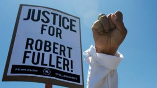 A sign reads 'Justice for Robert Fuller'