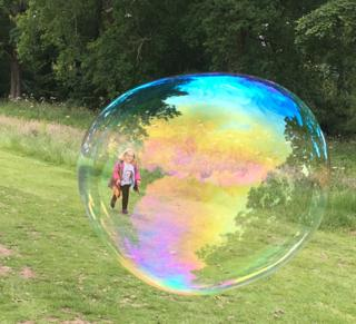 Girl chases a giant bubble