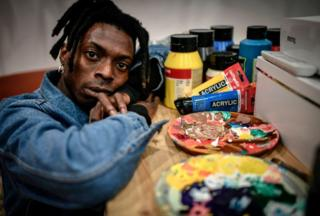Cameroonian artist Francis Essoua Kalu aka 'Enfant Precoce' poses at his workshop on February 6, 2019 in Paris.
