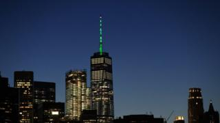 One World Trade Center glowing green against New York skyline