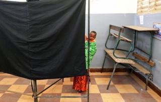 A woman carries a child as she casts her vote during the presidential election, at a polling station in Medina neighbourhood, Dakar, Senegal February 24, 2019