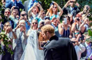 "Meghan Markle and Prince Harry kiss on the steps of St George""s Chapel at Windsor Castle following their wedding. Saturday May 19, 2018"