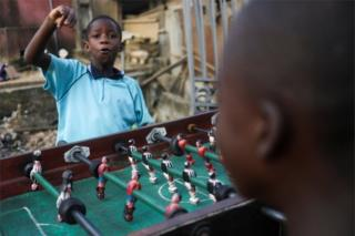 in_pictures A child punches the air as he plays table football with others.