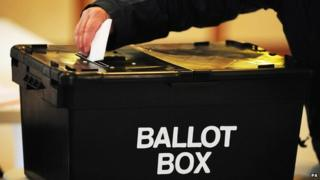 A voter puts their ballot paper into a ballot box