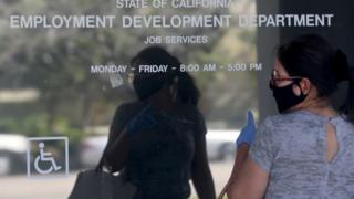 Woman outside closed California State Employment Development Department office due to coronavirus.