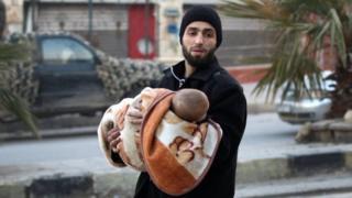 抱着婴儿的阿勒颇男性居民