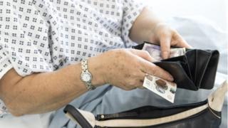 Female patient handing over money
