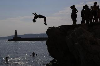 Young men leap off rocks into the Meditteranean Sea at Nice, south-eastern France