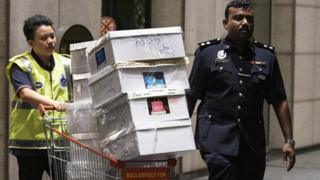 الشرطة تنقل الصناديق التي عُثر عليها