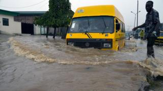 A public transport bus drives in a flooded Agege Motor Road, in the local Government Area of Mushin town, Lagos, on October 20, 2019. - Recent torrential rainfall has left many roads, homes and factories flooded, especially the chaotic traffic congestion occasioned by bad conditions of the roads, poor drainage and frequent breakdown of vehicles in Lagos, Nigeria's commercial capital.