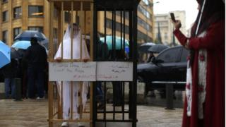 """Benzer bir yasanın bulunduğu Lübnan'da da yasanın iptal edilmesi için kampanyalar düzenleniyor. Beyrut'ta düzenlenen bu gösteride eylemcinin kendini kapattığı kafesin üstünde """"beyaz bir kıyafet tecavüzün üstünü örtmez"""" yazıyor."""