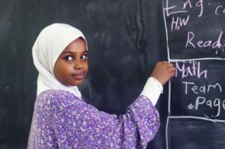 آلاء، التي يبلغ عمرها 12 عاما، تكتب على سبورة الصف في مدرستها في الخرطوم