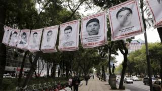 A pedestrian walks past banners with pictures of some of the 43 missing students of Ayotzinapa College Raul Isidro Burgos, along Reforma Avenue in Mexico City, Mexico September 29, 2015.