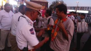 A police officer giving a man a flower garland to wear