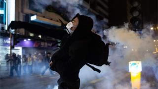 A protester reacts after police fire tear gas to disperse bystanders in a protest in Jordan district in Hong Kong, on early December 25, 2019