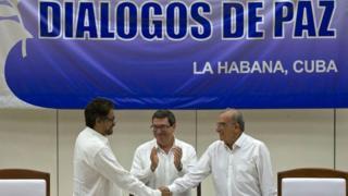 合意文書に署名した政府代表のデ・ラ・カレ氏(写真右)とFARCの交渉人マルケス氏(同左)。写真中央はキューバのロドリゲス外相(24日)