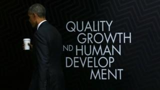 "US President Barack Obama leaves the stage after holding a press conference at the conclusion of the APEC Summit in Lima, Peru. Behind him the words ""quality growth and human development"". 20 November 2016."