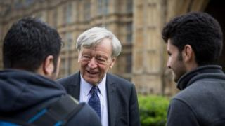 Lord Dubs speaks to two child refugees from Syria on College Green on 25 April