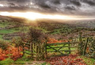 The sun rises over the countryside.