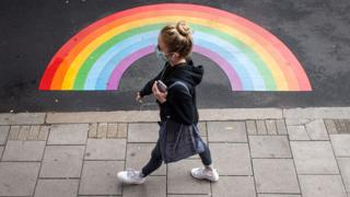 Woman in a mask walks past a rainbow painted on the floor