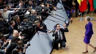 Theresa May walks towards a mob of cameras
