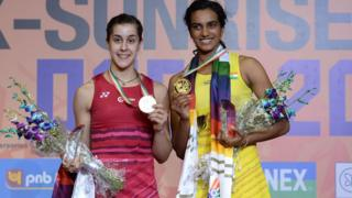 India's Pusarla V. Sindhu (R) poses with her gold medal, with Spain's Carolina Marin with her silver medal,